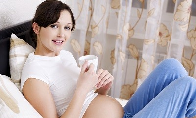 pregnant in bedroom with a cup